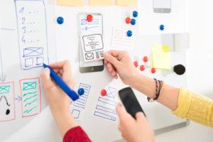 Sur tableau blanc des mains positionnent des schémas de pages web, crayon en main, smartphone en main